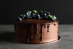 Fresh delicious homemade chocolate cake. With berries on table against dark background royalty free stock photo