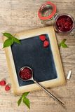 Fresh and  Delicious Homemade Raspberries Jam. Healthy Eating Concept with Fresh Raspberries on a Chalkboard. Selective focus Stock Photos