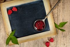 Fresh and  Delicious Homemade Raspberries Jam. Healthy Eating Concept with Fresh Raspberries on a Chalkboard. Selective focus Royalty Free Stock Image