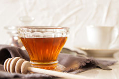 Fresh delicious honey in a crystal glass. On a light background royalty free stock image