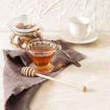 Fresh delicious honey in a crystal glass. On a light background stock photography