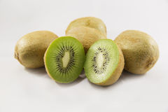 Fresh an delicious kiwis and a couple half kiwis on white and isolated background. Kiwis and a couple half delicious and fresh kiwis on white background stock photo