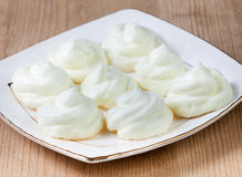 Fresh delicious meringues in a plate on table Royalty Free Stock Image