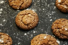 Fresh delicious oatmeal cookies with chocolate inside with powdered sugar on black textured background. Fresh delicious oatmeal cookies chocolate inside powdered stock images