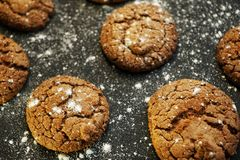 Fresh delicious oatmeal cookies with chocolate inside with powdered sugar on black textured background. Fresh delicious oatmeal cookies chocolate inside powdered royalty free stock photos