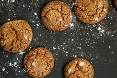 Fresh delicious oatmeal cookies with chocolate inside with powdered sugar on black textured background. Fresh delicious oatmeal cookies chocolate inside powdered stock image