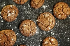 Fresh delicious oatmeal cookies with chocolate inside with powdered sugar on black textured background. Fresh delicious oatmeal cookies chocolate inside powdered stock photos
