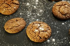 Fresh delicious oatmeal cookies with chocolate inside with powdered sugar on black textured background. Fresh delicious oatmeal cookies chocolate inside powdered stock photography