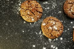 Fresh delicious oatmeal cookies with chocolate inside with powdered sugar on black textured background. Fresh delicious oatmeal cookies chocolate inside powdered royalty free stock photo