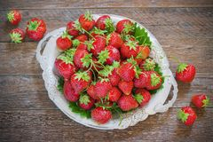 Fresh and delicious organic strawberries on old metal plate, wooden table. Perfect for your healthy eating dieting. Royalty Free Stock Image