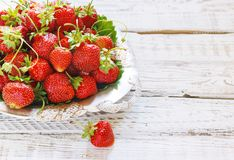 Fresh and delicious organic strawberries on old metal plate, wooden table. Perfect for your healthy eating dieting. Stock Photo