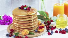 Fresh delicious pancakes with summer berries on light background. Honey is poured on a stack of delicious pancakes pancakes with summer berries, apricot, peach stock video