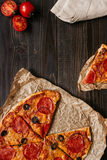 Fresh delicious pizza with pizza ingredients on the wooden table, top view Stock Photos