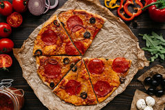 Fresh delicious pizza with pizza ingredients on the wooden table, top view. Fresh delicious sliced pizza with pizza ingredients on the wooden table, top view royalty free stock image