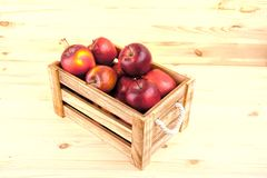 Fresh and delicious red  apples in a wooden crate on a white bac. Kground Royalty Free Stock Photos