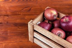 Fresh and delicious red  apples in a wooden crate on a white bac. Kground Royalty Free Stock Image