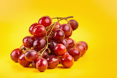 Fresh and delicious red grapes  on yellow background Stock Image