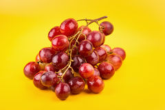 Fresh and delicious red grapes  on yellow background Royalty Free Stock Photography