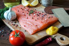 Fresh delicious salmon fillet with aromatic herbs, spices, garli. C, lemon on dark background. Top view. Closeup Stock Image