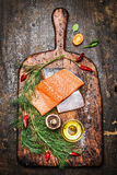 Fresh delicious salmon fillet with dill, oil and ingredients for cooking on rustic cutting board Royalty Free Stock Photos