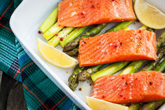 Fresh delicious salmon, green asparagus and lemon in pan. Raw fresh delicious salmon, green asparagus and lemon in pan, ready to cook Royalty Free Stock Photography