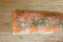 Fresh delicious salmon with parsley herbs isolated on a wooden table Royalty Free Stock Photo