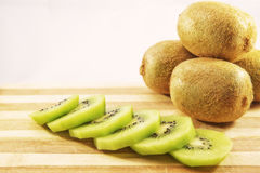 Fresh and delicious sliced kiwis on cutting board. In front of the kiwis royalty free stock images