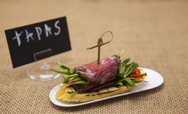Fresh delicious Spanish tapas with  roast beef with poster TAPAS on the textiles background . Great background for restaurant, caf Royalty Free Stock Images