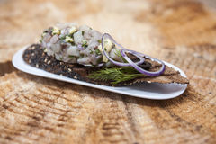 Fresh, delicious Spanish tapas with Tartar of herring and onions on a black baguette. An excellent background for the menus, cafe, Stock Images