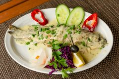 Fresh delicious trout in white creamy sauce, with vegetables on. A white plate. Close-up royalty free stock photos
