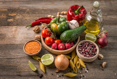 Fresh delicious vegetables, avocado and bottle of oil. Pasta and grains on table Stock Image