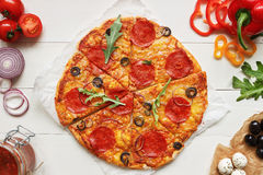 Fresh delisious sliced pizza with pizza ingredients on the wooden table, top view Stock Photos