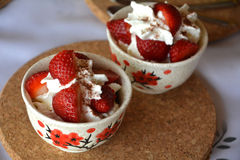 Fresh dessert with chopped strawberries and whipped cream on a bowl. Stock Image