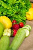 Fresh detailed fruit - strawberries, courgettes, lemon, apple and green salad Royalty Free Stock Photography