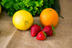Fresh detailed fruit - strawberries, lemon, orange and green salad Royalty Free Stock Photo