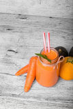 A fresh detox smoothie cocktail on a gray table background. A healthy carrot beverage in a mason jar. Copy space. A view from above on a mason jar full of a stock photos