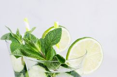 Fresh detox spring cocktail closeup with mint, lime, ice, cucumber, straw, bubbles, drops on soft white wooden background. royalty free stock photography
