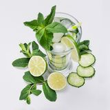 Fresh detox spring cocktail with mint, lime, ice, cucumber, straw as border on soft white wooden board, top view. stock photos