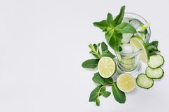 Fresh detox spring cocktail with mint, lime, ice, cucumber, straw as border on soft white wooden board, top view. stock photography