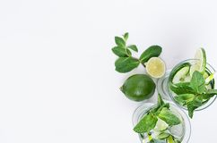 Fresh detox spring cocktail with mint, lime, ice, cucumber, straw as border on soft white wooden board, top view. stock images