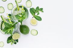 Fresh detox spring cocktail with mint, lime, ice, cucumber, straw as border on soft white wooden board, top view. Fun summer holiday background stock photos