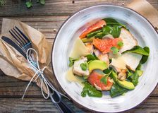 Fresh dietary salad of baked chicken breast, avocado, grapefruit slices, spinach leaves, cheese, olive oil and microgreen. Healthy food. Detox stock images