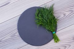 Fresh dill and slate on wooden background. Royalty Free Stock Images