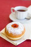 Fresh donut on a napkin with a cup of tea. Fresh sufgniya (donut) on a napkin with a cup of tea Stock Images