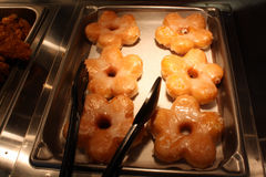 Fresh Donuts. Freshly made glazed donuts in a hot pan with tongs Royalty Free Stock Image