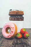 Fresh donuts for breakfast on the wooden table and fresh strawbe. Rry Royalty Free Stock Photography