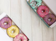 Fresh donuts with colorful glaze on the white wooden background. Copy space place Royalty Free Stock Image