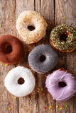 Fresh donuts with frosting close-up on the table. vertical top v Stock Photos