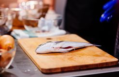 Fresh dorada fish on the wooden cutting board. In the kitchen Stock Photos
