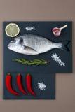 Fresh Dorado fish, chili pepper, garlic, lemon, rosemary and sal. T on black plates made of natural stone Royalty Free Stock Photos
